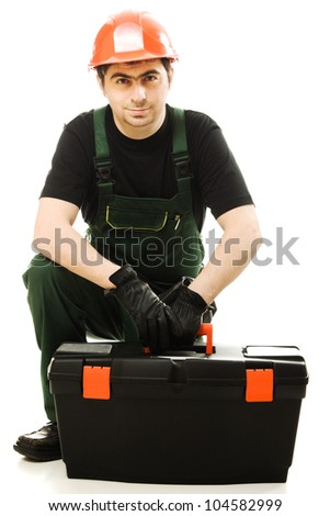 Service man wearing helmet and overall holding black toolbox over white