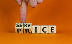 Service price symbol. Hand turns a cube and changes the words 'service' to 'price'. Beautiful orange background. Business and service price concept. Copy space.