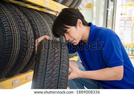 Service staff man touching and choosing for buying a tire in a supermarket mall. He was choose deliberately the right trade for the size of the wheel. Measuring rubber car wheel.