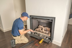 Service technician repairing a gas fireplace in a home