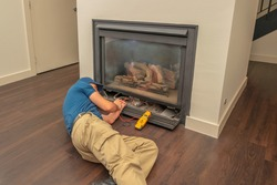 Service technician working on a gas fireplace inside of a residential home