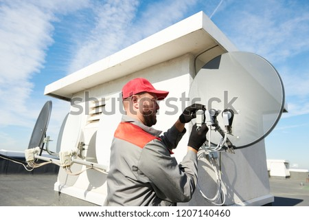 Service worker installing and fitting satellite antenna dish for cable TV