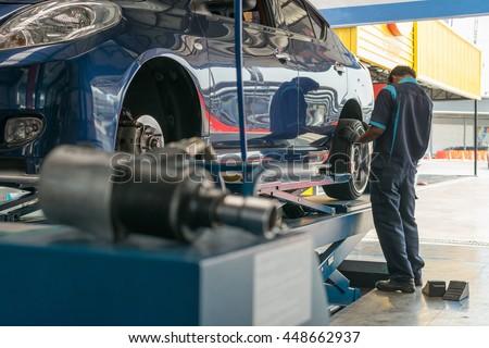 Serviceman checking suspension in a car at garage