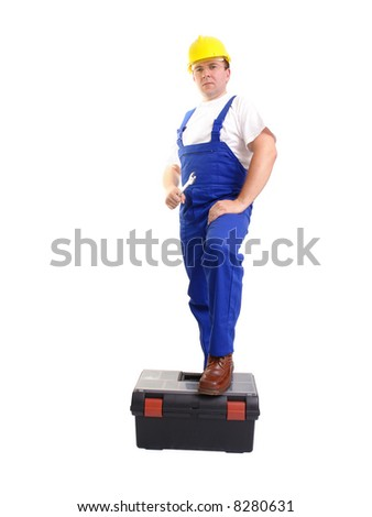 Serviceman wearing yellow helmet and blue overall holding flat wrench and resting his foot on black toolbox over white background