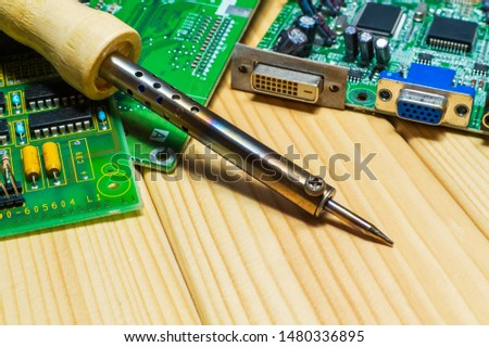 Services for the production of electronics and repair on a wooden background. A set of tools and electronic boards.