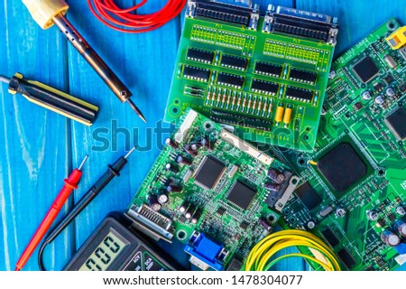 Services for the production of electronics and repair on a wooden blue background. A set of tools and electronic boards.