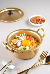 Serving a Korean style instant noodle, Ramyeon or Ramyun with spicy flavour topped with egg yolk, chilli, vegetables and kimchi in a traditional Korean noodle pot.