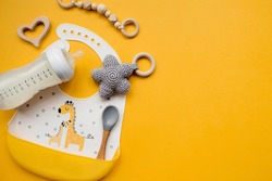 Serving baby food. Colorful silicone bib with giraffes, spoon and milk bottle on a trendy yellow background, flat lay.