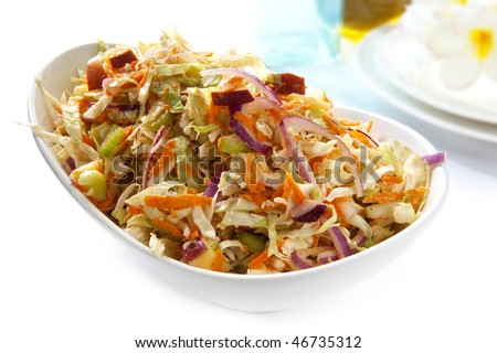 Serving bowl of coleslaw salad, made with cabbage, carrot, celery, onion and apple.