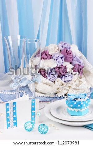 Serving fabulous wedding table in blue color on blue and white fabric background