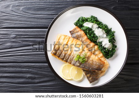 Serving fried sea bass fillet with spinach and lemon closeup on a plate on the table. horizontal top view from above Photo stock ©
