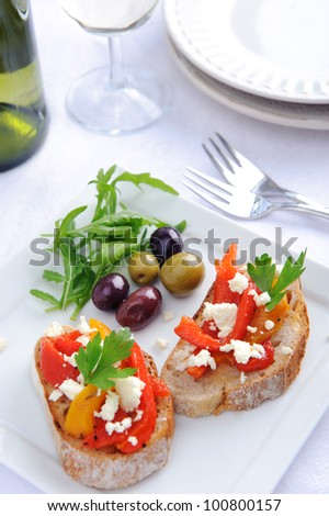 Serving of canapes; bread with roasted peppers and feta cheese and mixed olives served with wine
