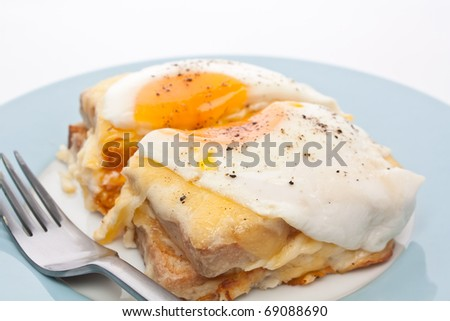 Serving of Croque Madame (Ham, Cheese, Bechamel Sauce and Egg Traditional French Toasted Sandwich) cut in half
