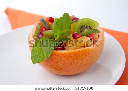 Serving of fresh fruit citrus salad in grapefruit peel. Kiwi, grapefruit, orange and pomegranate seeds.