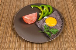 Serving of fried egg sunny side up prepared by beating egg white mixed with black olives and unbroken yolk, slices vegetables on brown dish on bamboo table mat