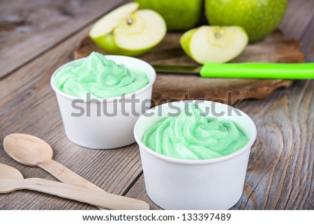 Serving of frozen homemade creamy ice yoghurt  with fresh green apples and wooden spoon