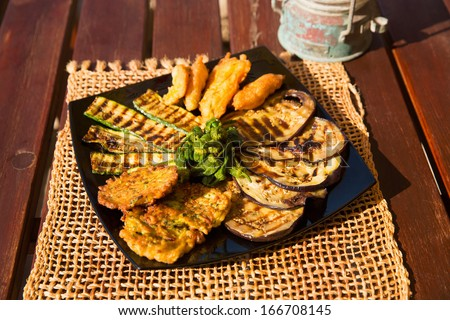 Serving of grilled zucchini, chicken and eggplant blue/Plate of plenty grilled food on picnic table. Lantern on serving table with serving plate. Grilled vegetable.