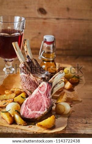 Serving of spicy seasoned barbecued lamb chops with roasted potatoes and onions in a rustic tavern served with a glass of red wine and beer
