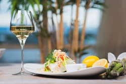 serving of steamed sea bass fillet on a plate in a restaurant, on a wooden table with white wine and decor