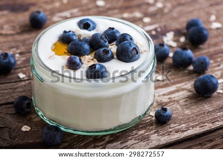 Serving of Yogurt with Whole Fresh Blueberries and Oatmeal on Old Rustic Wooden Table. Closeup Detail.