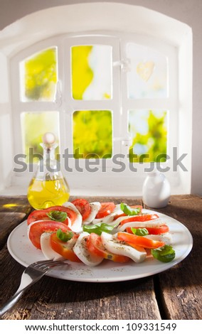 Serving on a plate of alternate slices of tomato and cheese salad with an oil dressing on a wooden table near a country window