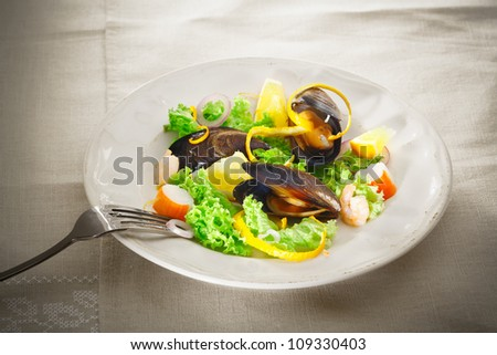 Serving on a plate of fresh mussel and seafood salad with leafy greens, crab and prawns garnished with orange peel