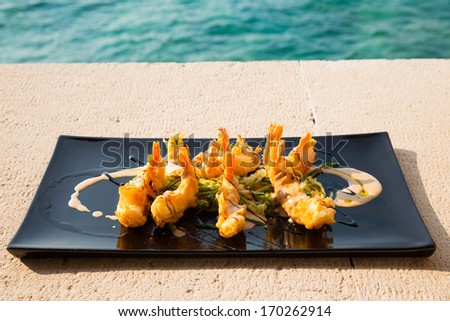 Serving plate with crispy shrimps and salad/Colorful dishware with seafood and vegetables. Delicious seafood serving on picnic table.