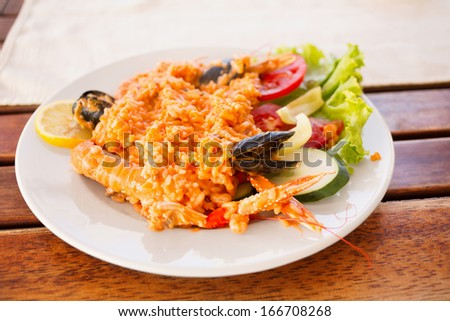 Serving plate with rice, shrimps and salad/Colorful dishware with seafood and vegetables. Delicious seafood serving on picnic table.