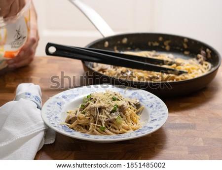 Serving Spaghetti al Funghi on a plate, wooden kitchen table  Foto d'archivio ©