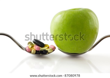 Serving spoon with green apple against a spoon full of pills, isolated on white background - stock photo