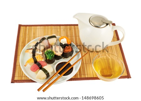 Serving sushi and tea composition on a bamboo mat isolated over white background
