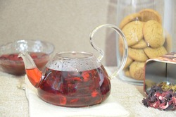 Serving table for breakfast, red tea in teapot. tea leaves, hibiscus