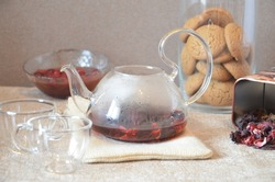 Serving table for breakfast, red tea in teapot. tea leaves, hibiscus and two glass cups for tea