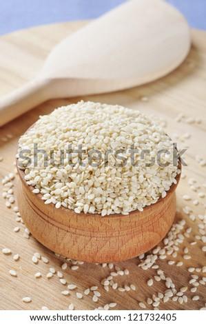 Sesame seeds in wooden bowl closeup.