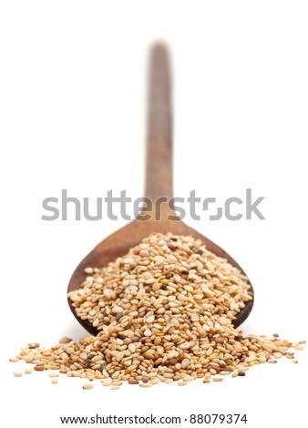 Sesame seeds on wooden spoon over white background