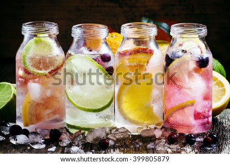 Set cold citrus lemonade: lemon with black currant, orange, lime and cranberry, grapefruit and bloody orange with crushed ice in a small bottle, selective focus