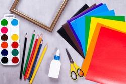 Set for application: paper, glue, scissor, paints, frame on a gray background