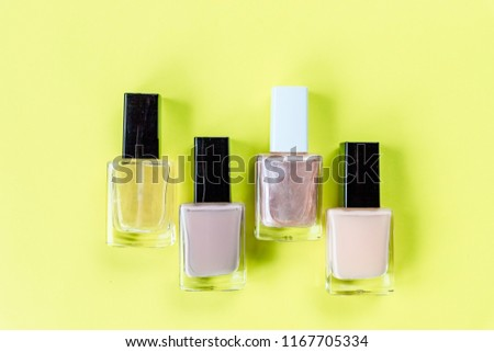 set for nail polish on yellow table background top view mock up.collection of various nail polish bottles.Nude collors. Nails care. Manicure, pedicure beauty salon
