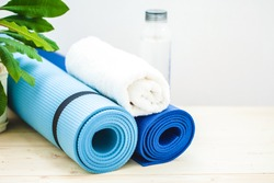 set for sports, a yoga mat, a towel, a bottle of water on a light background. The concept of a healthy lifestyle. Copy space