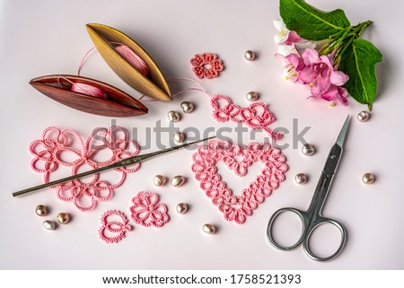Set for weaving lace tatting on a pink background. Two wooden shuttles with threads and lace examples in the form of hearts, pink pearls, a thin crochet hook and small scissors. Needlework. Photo stock ©
