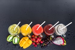 Set Fresh Range Color Juices Smoothie Green Yellow Red Violet White from Tropical Fruits Kiwi Mango Strawberry Grapes Dragon Jar Rainbow Dark Background Top View