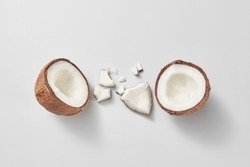Set from freshly brocken ripe natural organic exotic coconut fruit on a light grey background with soft shadows and copy space. Vegan concept. Top view.