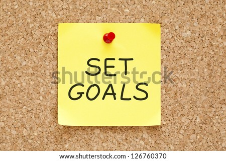 Set Goals on yellow sticky note pinned with red push pin on cork board.