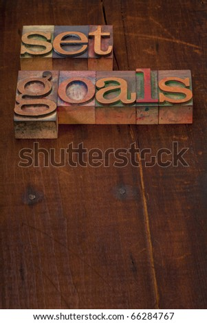 set goals - text in vintage wooden letterpress printing blocks against old grunge wooden background