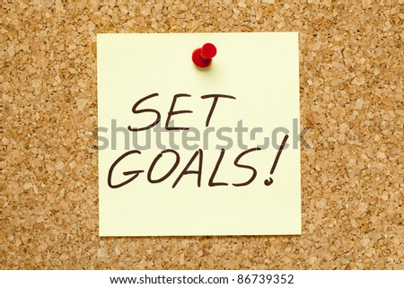 SET GOALS! written on an yellow sticky note on an office cork bulletin board.