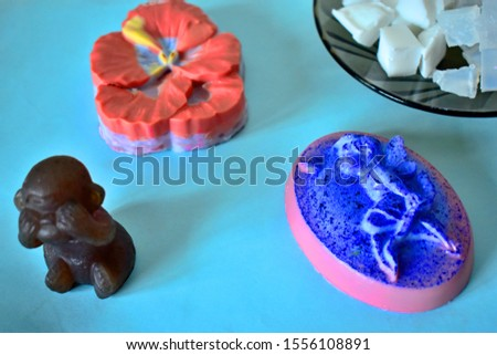 Set in the shape of soap and the basis for soap making on a blue background. 3D monkey, 2D fairy and Pansy flower.