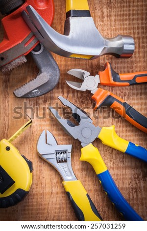 set o f tools on wooden board tapeline adjustable wrench hammer nippers pliers