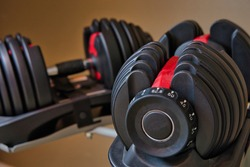 Set of adjustable dumbbells isolated on tan and brown background. Weights for working out at home.