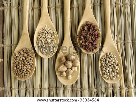 Set of Allspice, peppercorns and peppercorns, nutmeg seeds on wooden spoon