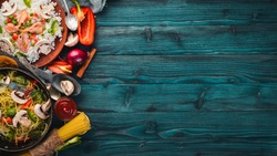 Set of Asian cuisine. Risotto with shrimps noodles with vegetables. Seafood. On a wooden texture background. Top view. Free space.